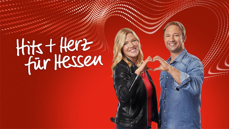 """Tanja und Tobi stehen nebeneinander vor einem roten Hintergrund. Mit ihren Händen formen sie gemeinsam ein Herz. Tanja trägt eine schwarze Lederjacke, Tobi ein Jeanshemd. Links im Bild steht der Schriftzug """"Hits und Herz für Hessen"""" in verschnörkelter Schrift."""