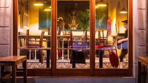 In einem Restaurant im Berliner Stadtteil Friedrichshain stehen die Stühle auf den Tischen.