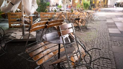 Baden-Württemberg, Stuttgart: Stühle im Außenbereich eines Restaurants stehen eine halbe Stunde nach der coronabedingten Sperrstunde am Hans-im-Glück-Brunnen zusammen.