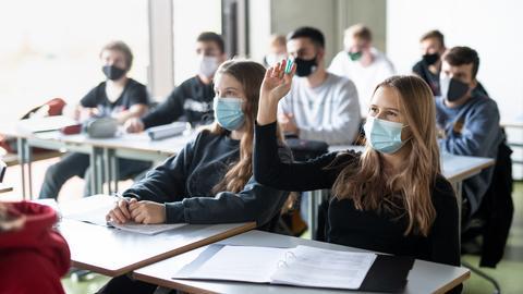 Schülerinnen und Schüler nehmen mit Mund- und Nasenschutz am Unterricht in einem Geographie-Seminar in der Jahrgangsstufe elf am staatlichen Gymnasium Trudering teil.