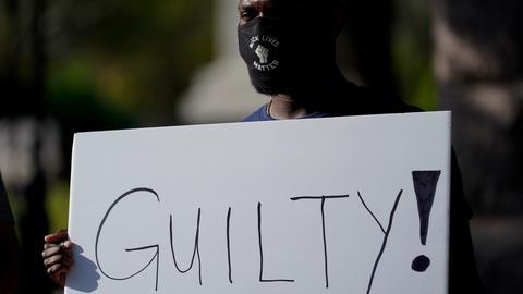 Mike James steht mit einem Schild mit der Aufschrift «Guilty» (schuldig) vor dem texanischen Kapitol.