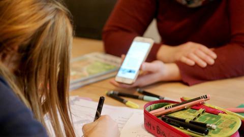 Eine alleinerziehende Mutter (r) hilft ihrer zwölfjährigen Tochter beim Homeschooling und hält ein Smartphone in der Hand.