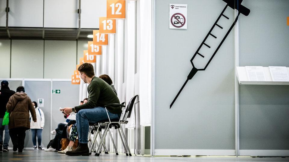 Menschen warten in einem Impfzentrum.