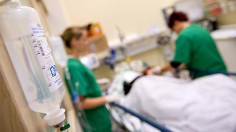 Medizinisches Personal versorgt im Krankenhaus einen Patienten.