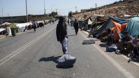 Griechenland, Lesbos: Migranten versammeln sich am Straßenrand während die Polizei mit Bussen den Zutritt zur Stadt Mytilini blockiert.