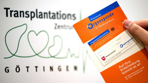 """Eine Frau hält in der Universitätsklinik Göttingen eine Broschüre des """"Netzwerk Organspende in Niedersachsen"""" in der Hand"""
