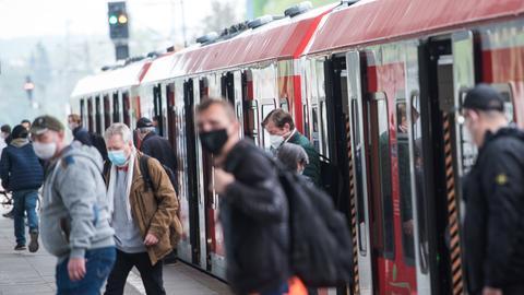 Fahrgäste mit Gesichtsmasken steigen aus einer S-Bahn aus.
