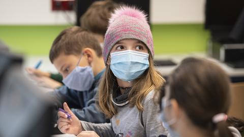 Mit Mund-Nase-Masken sitzen Schülerinnen und Schüler der fünften Klasse eines Gymnasiums in Frankfurt im Unterricht.