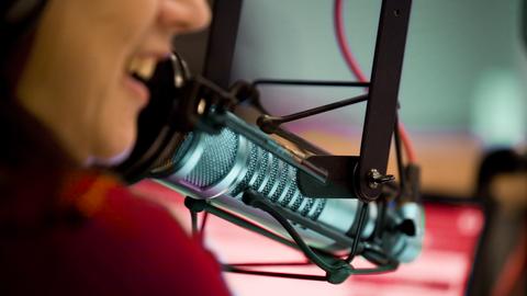 Eine Frau spricht in einem Hörfunkstudio in ein Mikrofon
