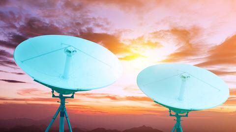Zwei Satelitenschüsseln vor Wolkenhimmel