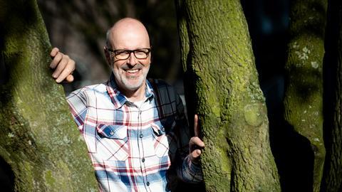 Peter Wohlleben steht an einem Baum.