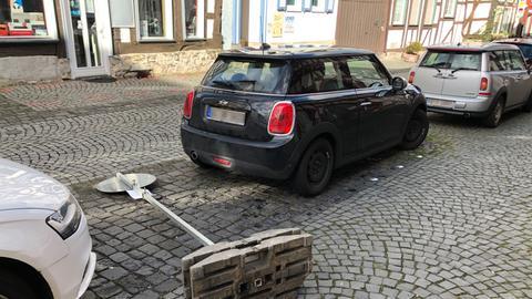 Ein umgefallenes Verkehrsschild liegt zwischen zwei parkenden Autos