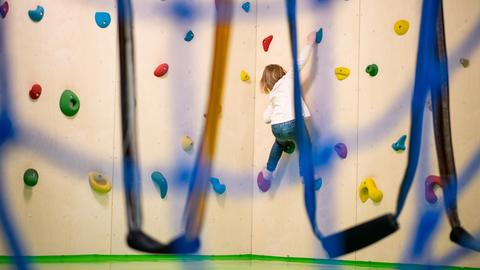Ein kleines Mädchen klettert eine Kletterwand hoch.