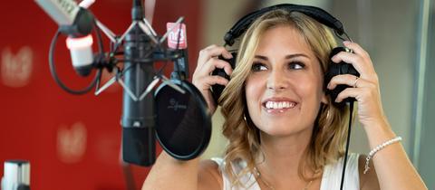 hr3-Moderatorin Kate Menzyk im Studio mit Kopfhörer und vor Mikrofon