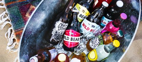 Bierflaschen liegen in einer Wanne zum Kühlen
