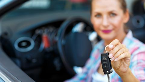Eine Frau sitzt im Auto und hält einen Autoschlüssel in der Hand