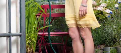 Eine Frau gießt ihre Balkonpflanzen