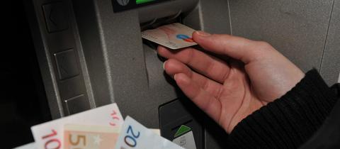 Eine Bankkundin hebt Geld am Automaten ab