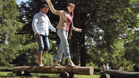 Ein Mann und eine Frau balancieren über einen Baumstamm