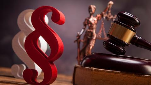 Paragraphen, Hammer und Justitia-Figur als Symbolbild für Justiz