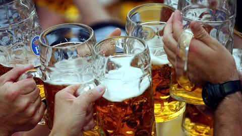 Besucher stoßen im Hofbräu-Festzelt auf dem Münchner Oktoberfest mit ihren Bierkrügen an.