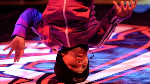 Ein Junge zeigt seine Breakdance-Choreographie auf der Bühne