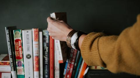 Eine Frau nimmt ein Buch aus einem Bücherregal