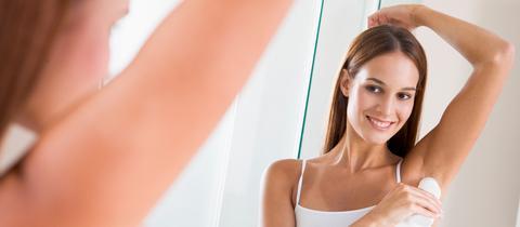 Frau steht vorm Spiegel und nutzt einen Deoroller