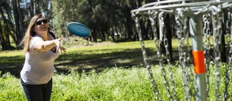 Frau wirft Frisbeescheibe im Park