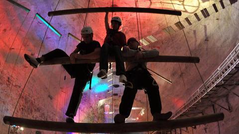 Junge Leute klättern im Erlebnis Bergwerk in Merkers-Kieselbach an der so genannten Himmelsleiter empor.