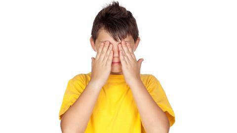 Ein Junge hält sich die Hände vor die Augen