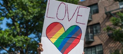 """Schild mit der Aufschrift """"Love wins"""" und einem Herz in Regenbogenfarben"""