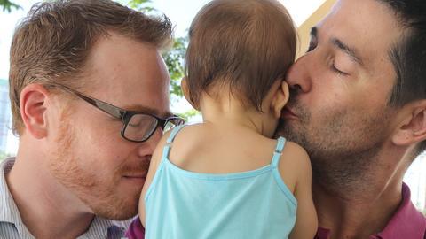 Zwei Männer küssen ihr gemeinsames Kind