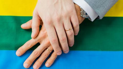 Zwei Männerhände mit Eheringen liegen auf einer Regenbogenflagge