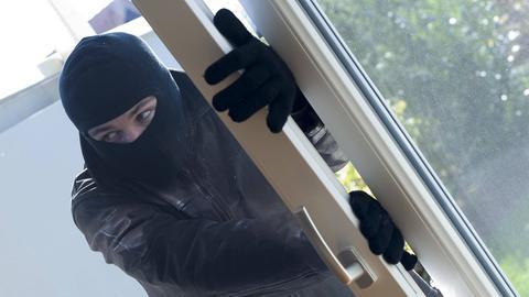 Einbrecher steigt durch Fenster