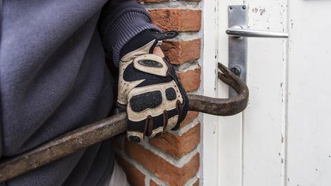 Einbrecher versucht mit Brecheisen eine Tür zu öffnen