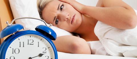 Frau liegt wach im Bett und schaut auf Wecker