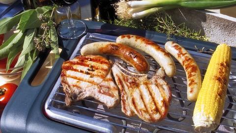Elektrogrill mit Fleisch und einem Maiskolben