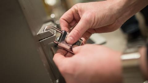 Ein Mann versucht das Zahlenschloss in einem Escape Room zu öffnen