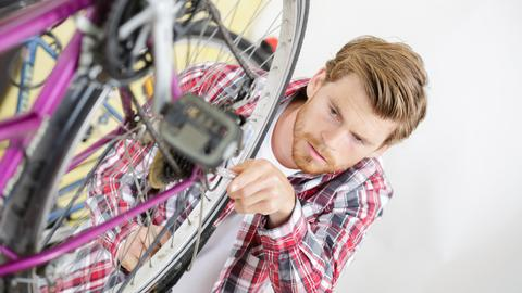 Ein Mann schraubt am Hinterrad seines Fahrrads
