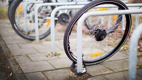 Ein zurückgelassenes Hinterrad von einem Fahrrad steht an einem Fahrradständer.
