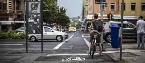 Eine Fahrradfahrerin wartet in Wiesbaden auf dem Radweg, bis sie weiterfahren kann