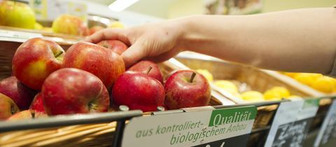 Eine Frau greift nach einem Apfel aus dem Obst- und Gemüseregal eines Reformhauses.