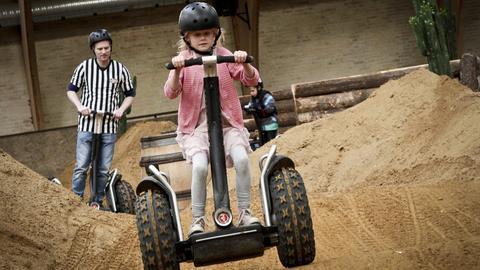 Ein Mädchen und Mann fahren Segway im Indor-Park