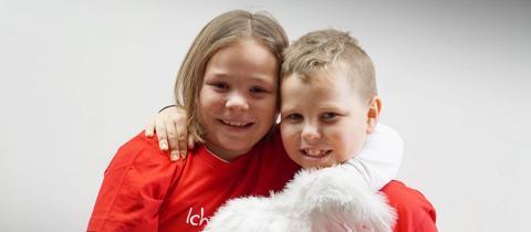 Die Geschwister Lina und Finn umarmen sich.