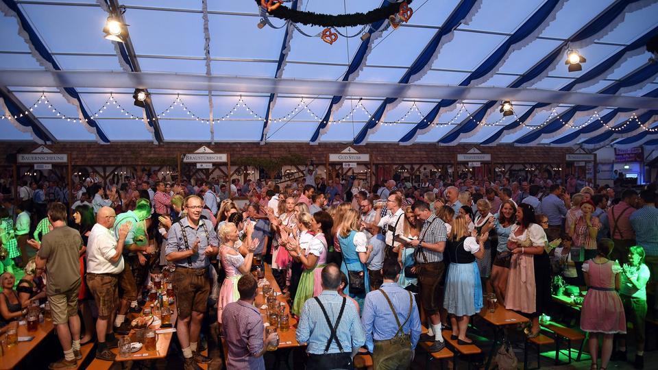 Menschen tanzen auf den Bänken auf dem Frankfurter Oktoberfest