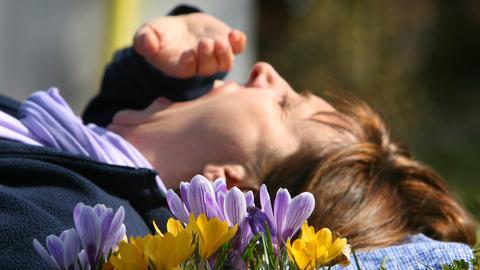 Eine Frau liegt gähnend im Gras