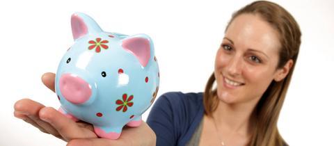 Eine junge Frau hält ein Sparschwein in der Hand