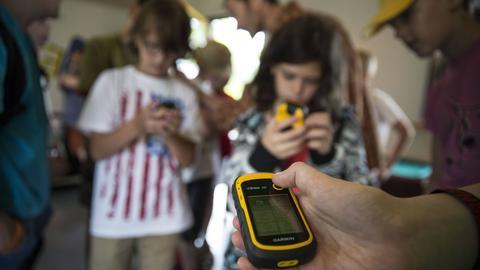 Geocaching: Kinder halten ein Navigationsgerät in der Hand
