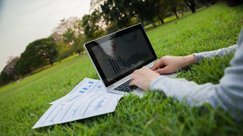 Ein Laptop liegt im Gras und ein Mann arbeitet daran